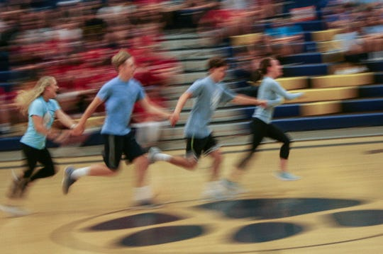The relay race requires a coordinated efforts as four teammates hold hands to run a lap.