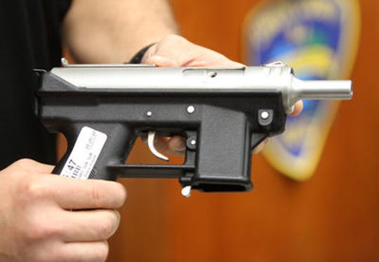 Union County Prosecutor's Office weapons expert Detective Dan Seib holds a Intratec 9mm (Tec-9) that was among nearly five hundred firearms purchased in a 2014 Union County gun buyback program.