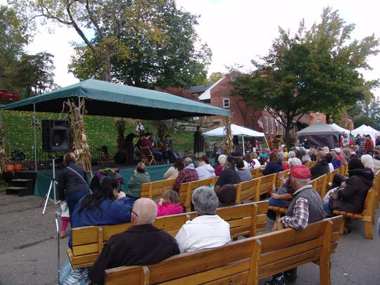 Visitors gather around the main stage at the Apple Butter Stirrin' Festival to listen to bluegrass music.
