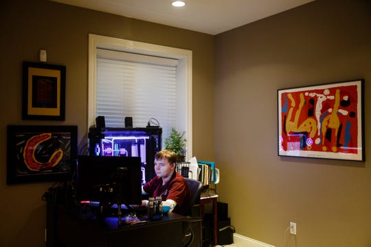 An avid gamer, Henry DeAngelis, 18, finishes some homework before turning to a game on his computer. DeAngelis has epidermolysis bullosa, a disease that makes his skin very fragile and often leads to skin cancer.