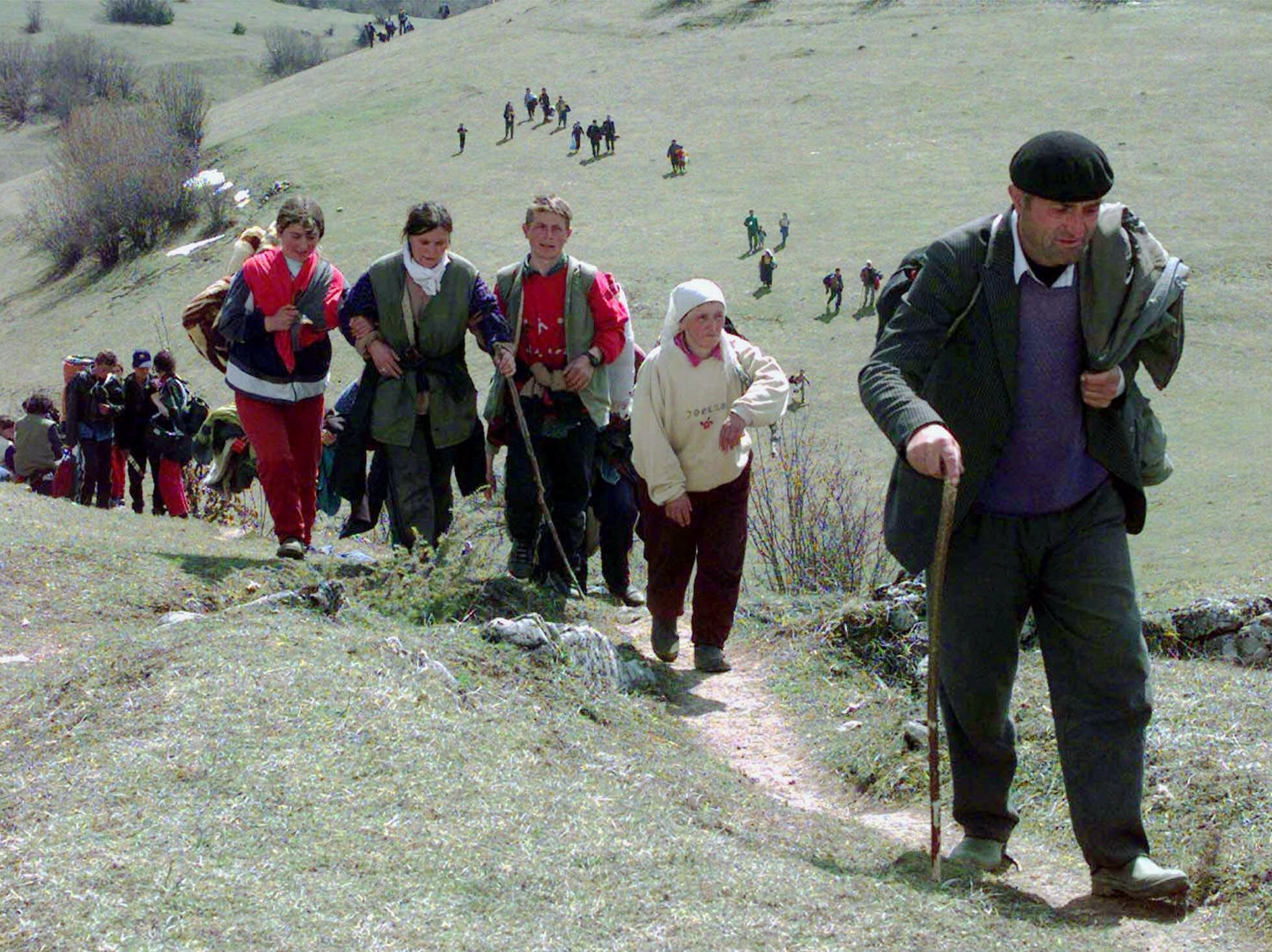 Kosovo refugees from several villages near Istok walk the muddy paths of the Montenegrin village of Jablanica, near the border of Serbia and Kosovo, on their way to the refugee camps of Rozaje, Thursday, April 8, 1999. More than 35,000 Kosovars have been flooding Montenegro since NATO airstrikes in Yugoslavia.
