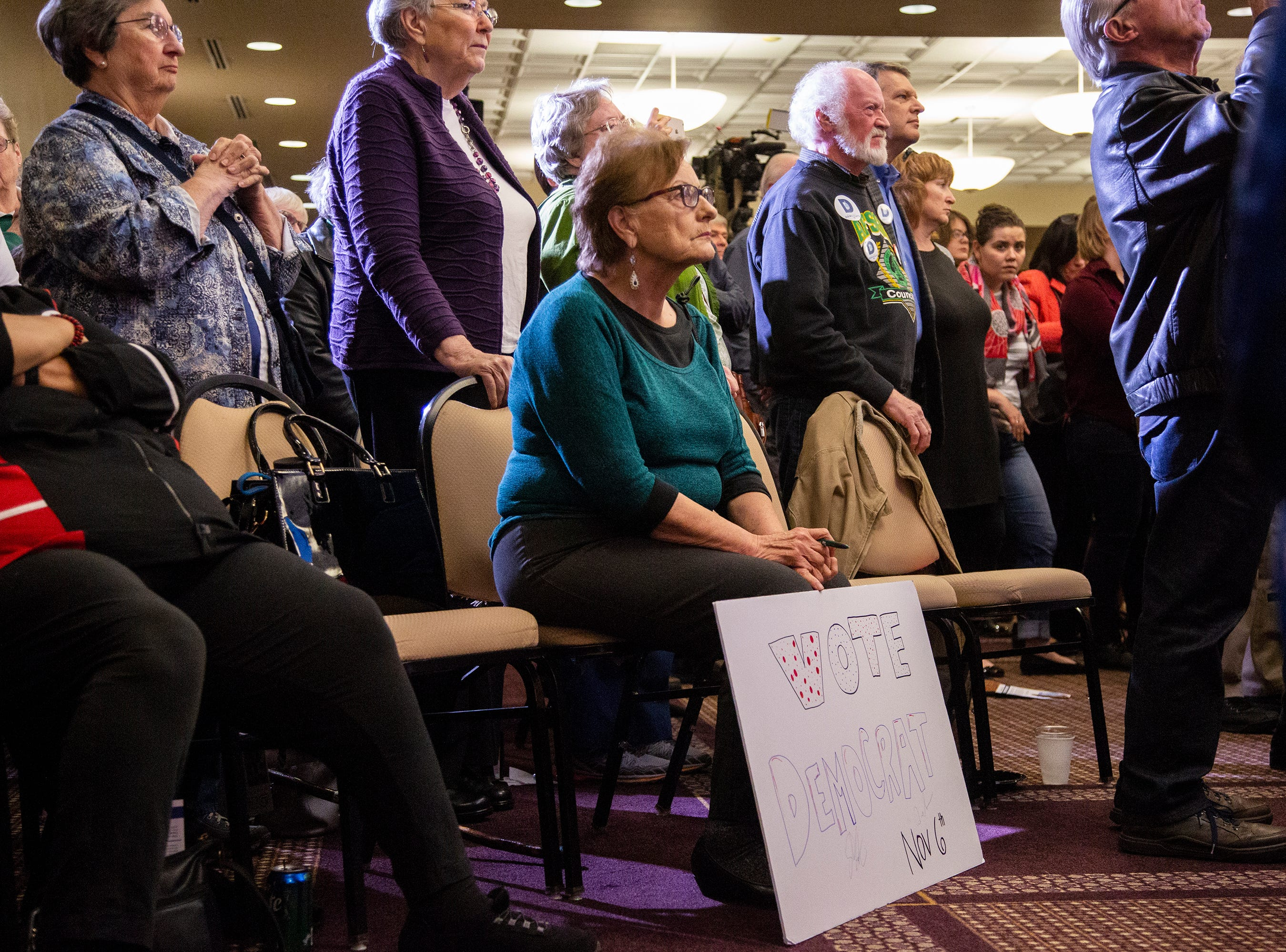 Karon Finn, of Grimes, holds a sign while listening to Kamala Harris, a Democrat Senator from California, during a rally with Polk County Democrats on Monday, Oct. 22, 2018, in Des Moines.