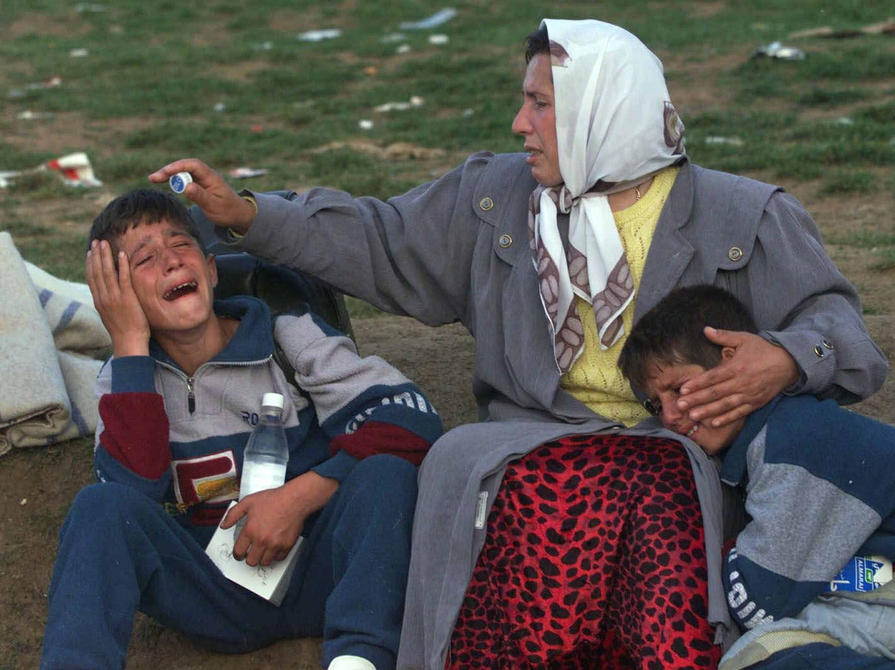 An ethnic Albanian woman consoles her two twin sons at the Morini, Albania, border after crossing on foot from Kosovo Tuesday May 25, 1999. Kosovar refugees continued to cross into neighboring Albania as NATO tries to relocate the over-crowded camps further south from the volatile border area. (AP Photo/David Guttenfelder)-