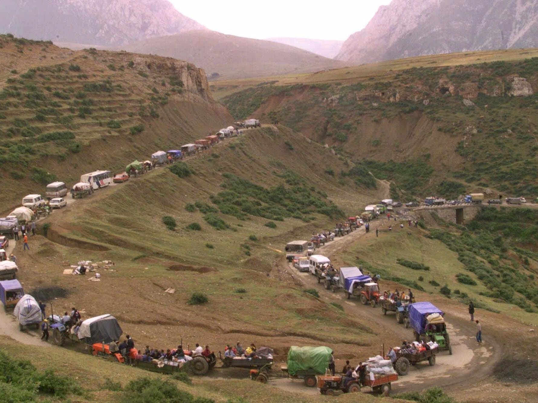 Ethnic Albanian refugees wind through the northern Albanian mountains on their way to the Kosovo border Friday June 18, 1999. Many thousands of refugees have packed up and left the tented camps of Kukes, Albania in the past 72 hours, returning to their native Kosovo after the arrival of NATO troops on the ground.