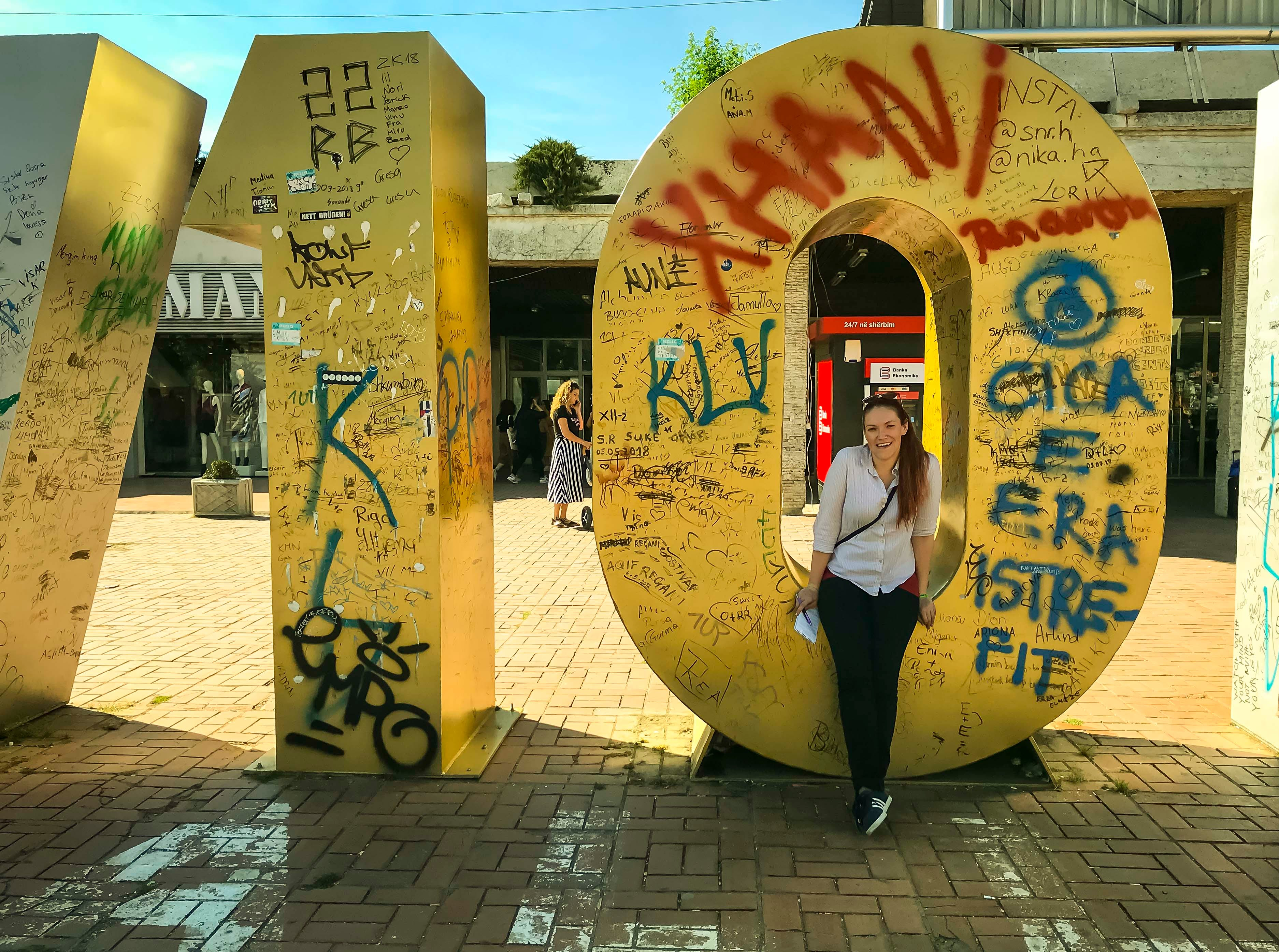 """Courtney Crowder, the Register's Iowa Columnist, in front of the Newborn Monument in Pristina, Kosovo, Tuesday, Sept. 18, 2018. The monument was placed in Feb. 2008 after the Republic of Kosovo formally declared its independence from Serbia. The """"B"""" & """"O"""" have been replaced this year with """"10"""" to mark the tenth anniversary of Kosovo independence."""