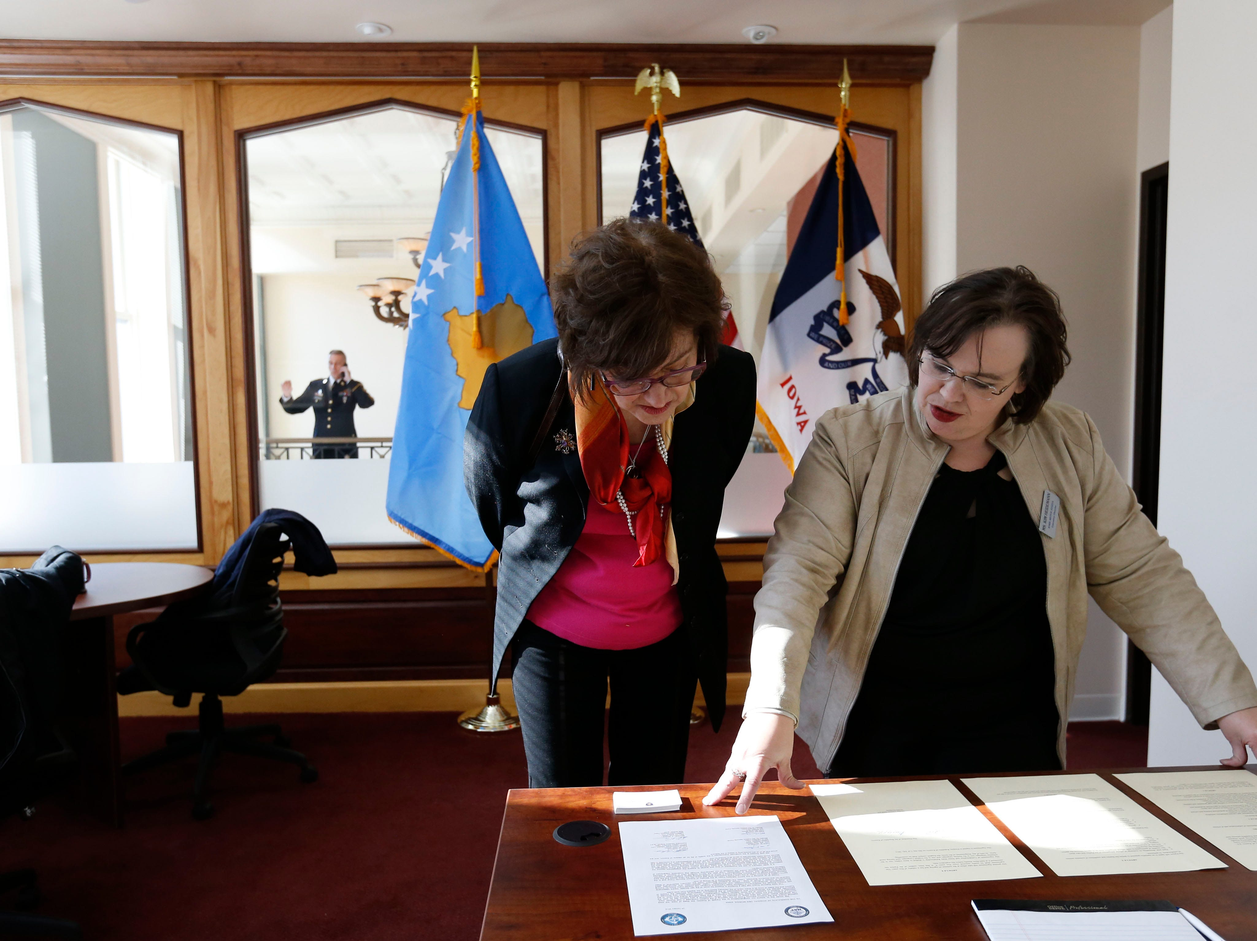 Deborah Loers (center) and Kim Heidemann, director of the Iowa Sister State program, look over the official documents making the agreement possible Friday, Jan 29, 2016, during a reception for the opening of the Consulate of the Republic of Kosovo inside The Saddlery Building on Court Avenue in Des Moines.