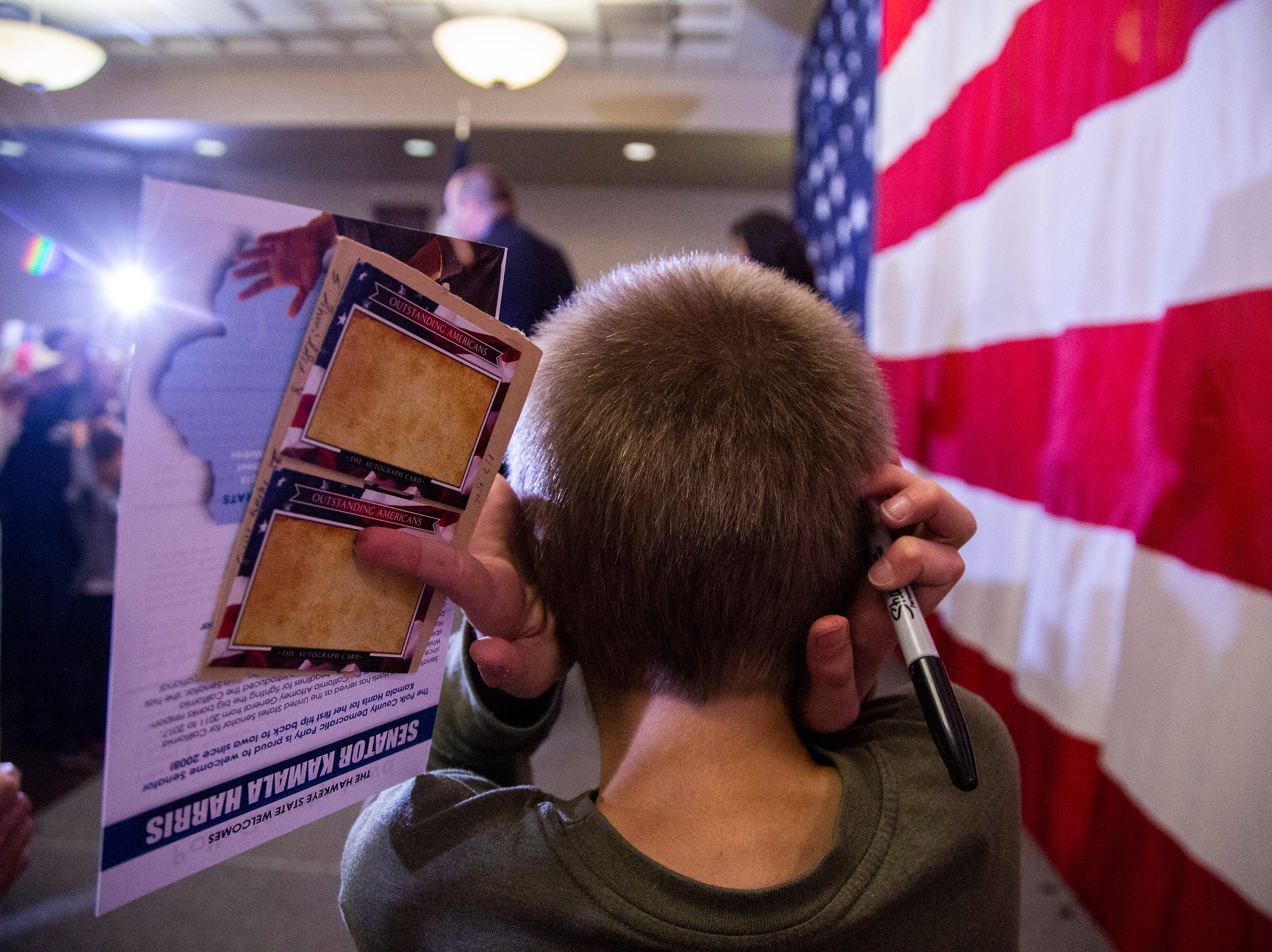 A young boy covers his ears as the crowd cheers for Kamala Harris, a Democrat Senator from California, during a rally with Polk County Democrats on Monday, Oct. 22, 2018, in Des Moines.