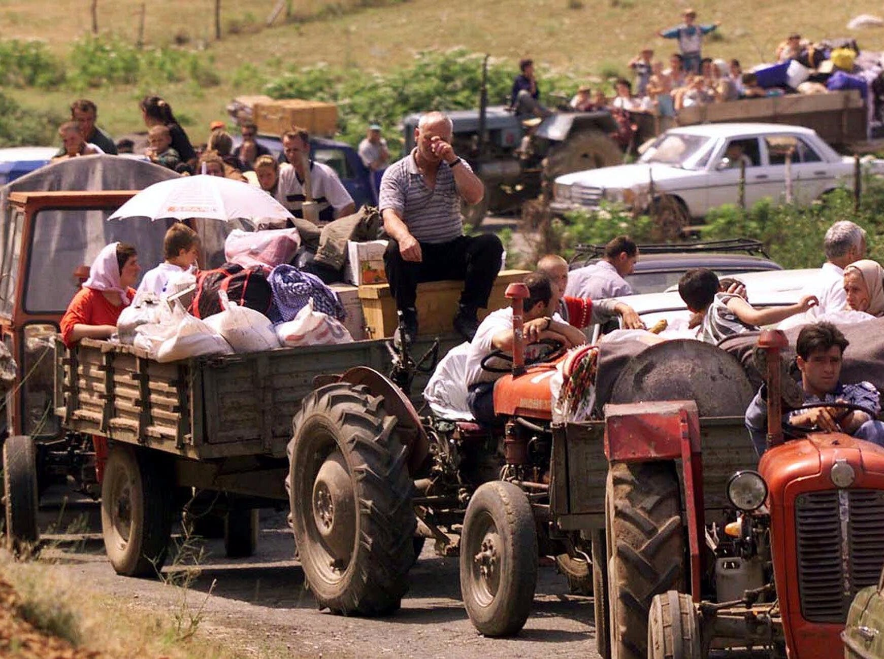 Thousands of refugees, backed up for miles, make their way into Kosovo near the border crossing at Morini, Albania, Wednesday, June 16, 1999, despite warnings of minefields and little food.