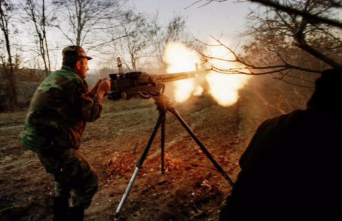 A Kosovo Liberation Army soldier fires on Serbian military positions as the Serbs looted and shelled villages near Vucitern, 30 km (18 miles) northwest of Pristina in Kosovo Wednesday March 10, 1999. The region has been a focus for Serbian forces who have shelled and looted villages over the past two weeks.