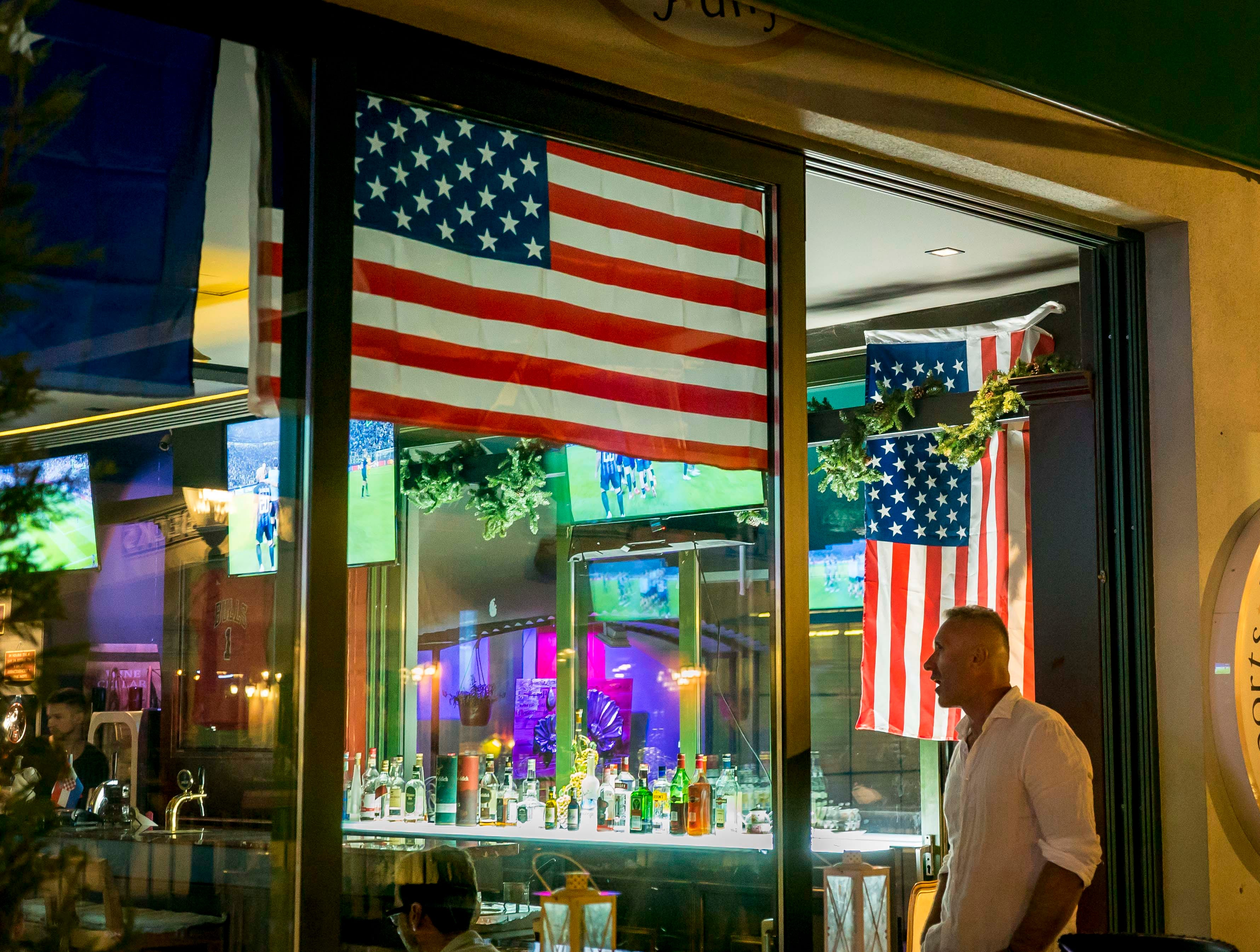 U.S. Flags and an Iowa State Cyclones banner hang in Sports Bar President at Marigona Residence in Pristina, Kosovo, Tuesday, Sept. 18, 2018.