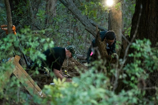 In this Monday, Oct. 22, 2018, photo, detectives investigate the scene where remains believed to be those of a southwestern Michigan woman who disappeared in 2010 were found, in Fulton, Mich. Doug Stewart, who was convicted of killing his estranged wife in 2011, took police to the burial site Monday.