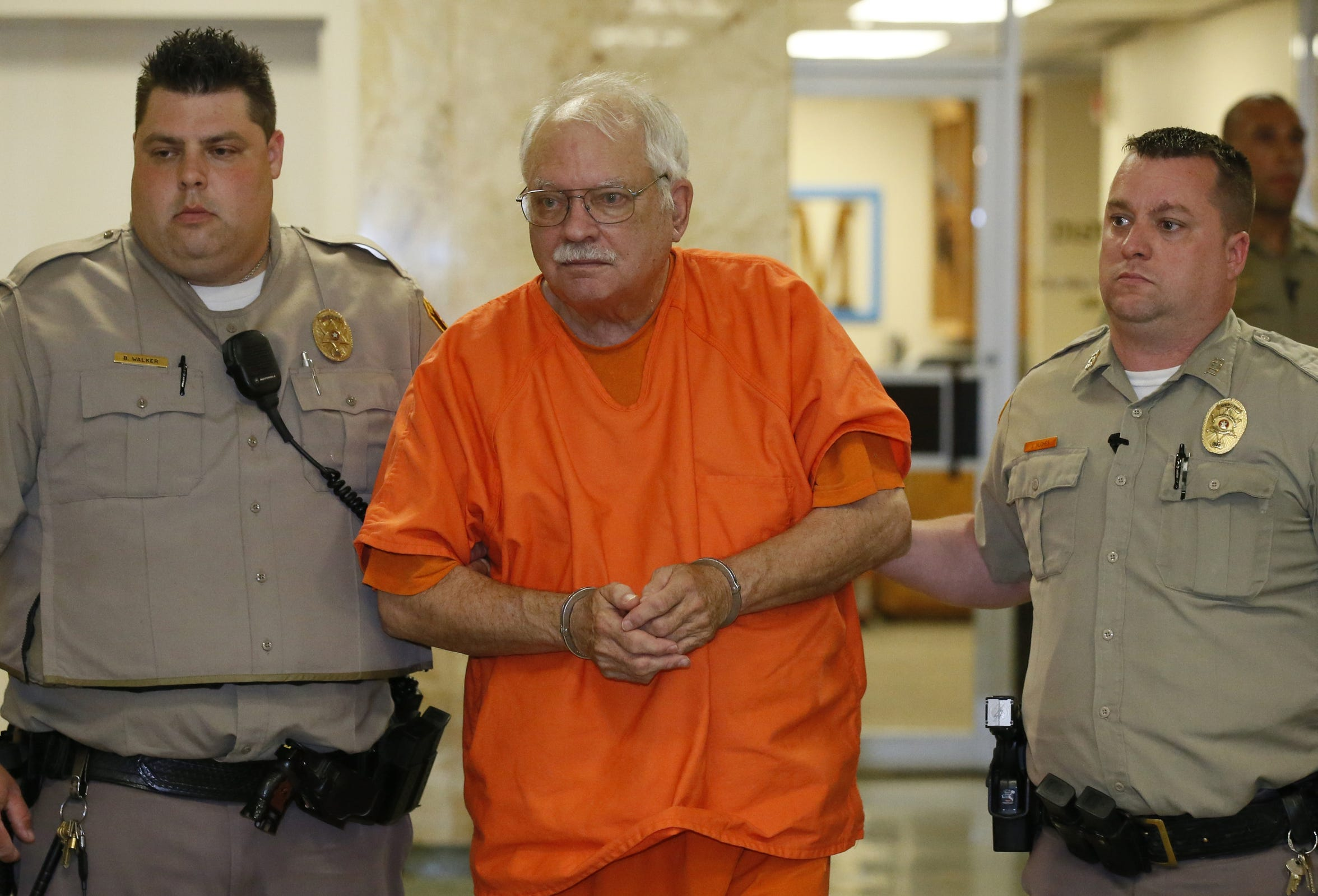 Robert Bates, a former Oklahoma volunteer sheriff's deputy who said he mistook his handgun for his stun gun when he fatally shot an unarmed suspect last year, is escorted from the courtroom following his sentencing at the courthouse in Tulsa, Okla., Tuesday, May 31, 2016. Bates, who was convicted of second-degree manslaughter, was sentenced to four years. (AP Photo/Sue Ogrocki)