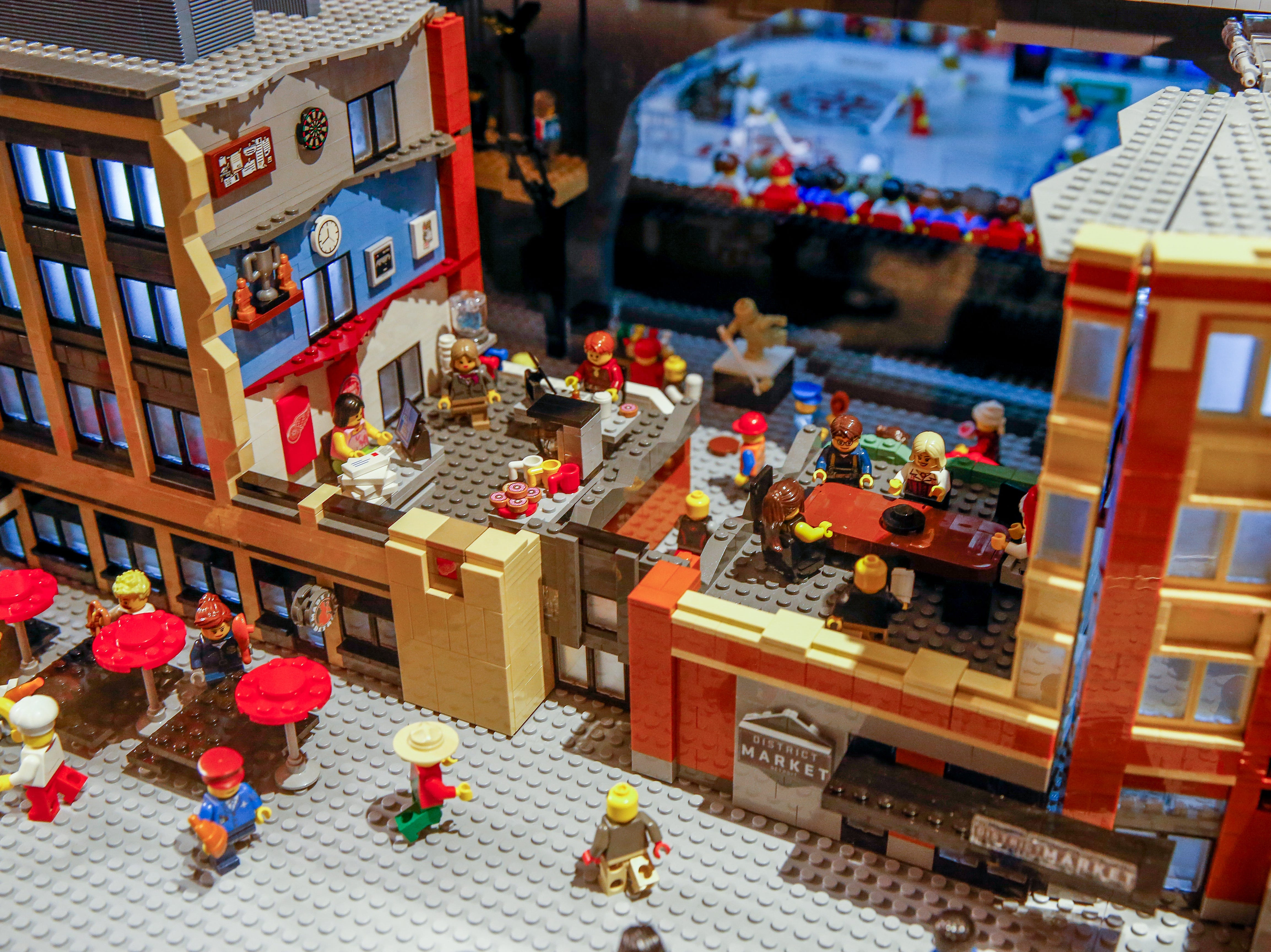 LEGO patrons dine at the District Market. A game can be seen in this cutaway view, as well as the statue of Gordie Howe.