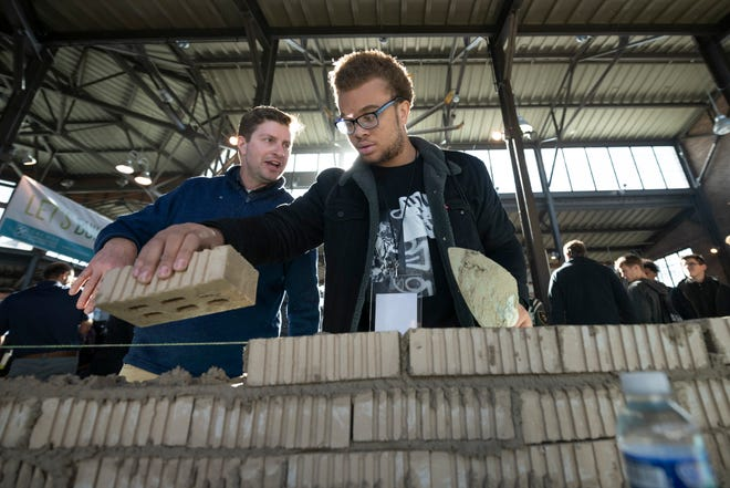 Antonio Thomas, right, of Warren Mott high school, tries his hand at laying bricks under direction from Brad Maurer, of Leidal and Hart Mason Contractors during the third annual Sachse Construction Academy at Eastern Market in Detroit, Tuesday.