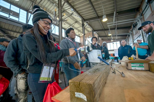 Irionna Lucas of Harper Woods High School tries hammering in a nail during the third annual Sachse Construction Academy at Eastern Market in Detroit on Tuesday.