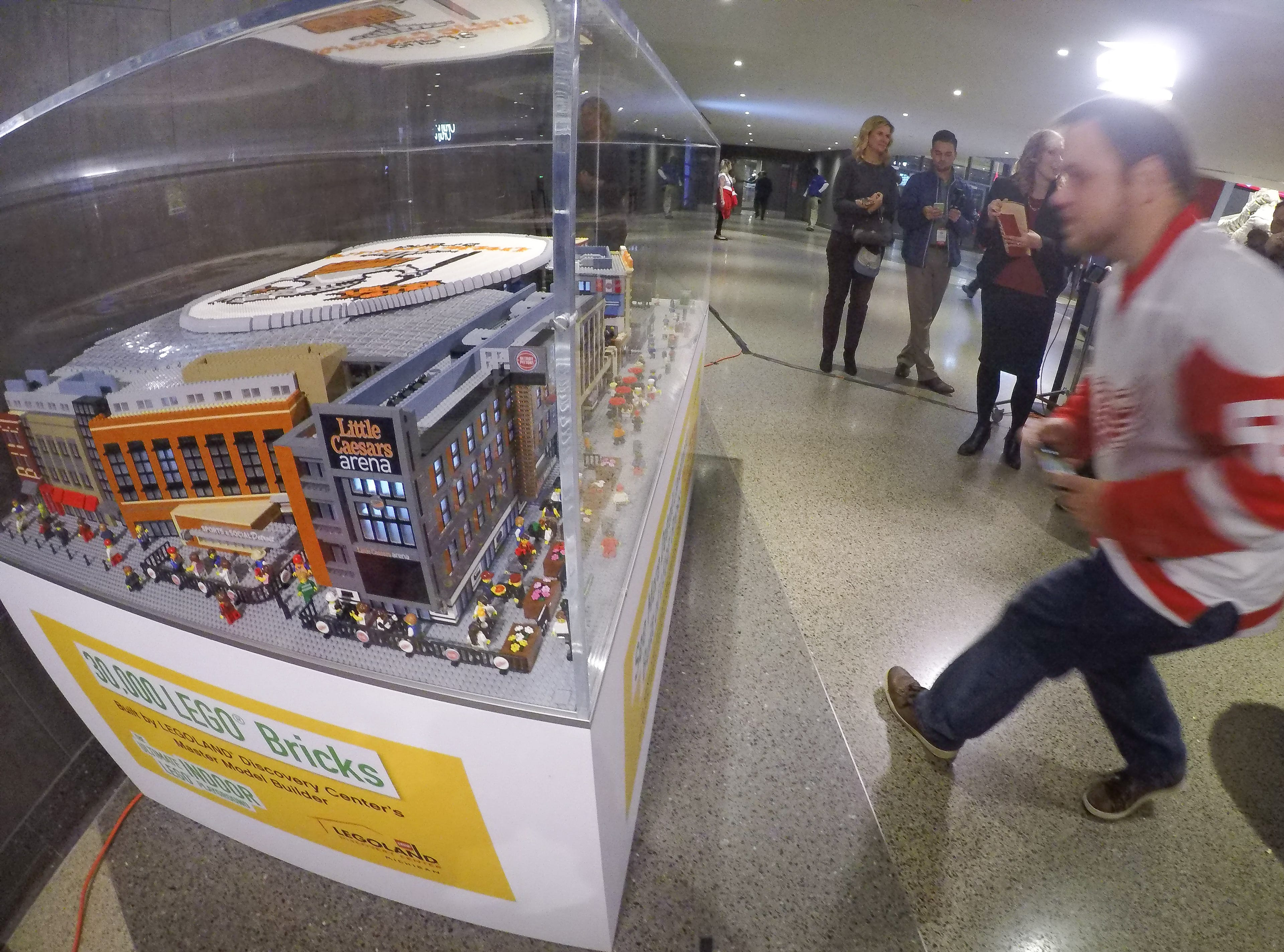 A Red Wings fan jumps in to get a close up picture of the 30,000-piece model of Little Caesars Arena, now located in the northwest corner of the stadium near the Gordie Howe statue. It was unveiled during Monday's game.