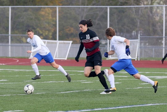 Noah Sperduto of Elmira dribbles between Ian Aepelbacher (12) and Connor Thorpe (20) of Horseheads.