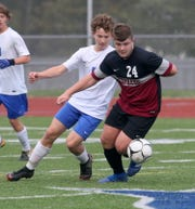 Evan Moore of Elmira dribbles the ball in front of Riley Schwab of Horseheads.