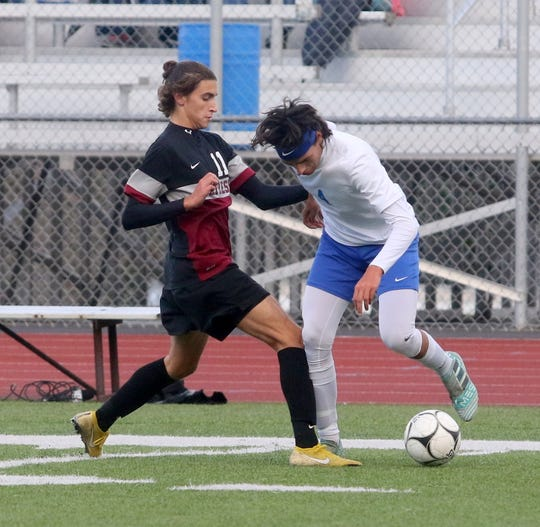 Cameron Kelly-Hobbs, left, of Elmira and Chris Enright of Horseheads battle for possession.