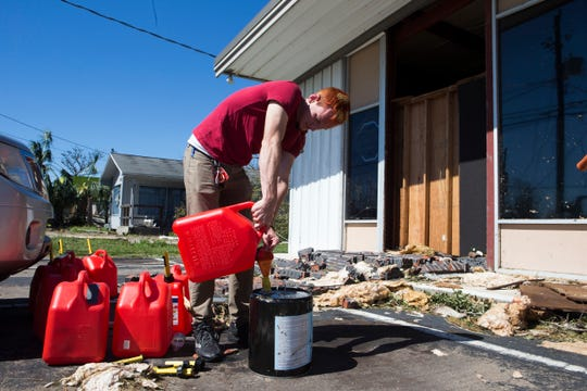 Austin Stephens fills gas tanks to give to those in need in Panama City,Fla. after Hurricane Michael on Friday, October 12, 2018. Transmitted for Panama City News Herald by Northwest Florida Daily News via AP. (Joshua Boucher/News Herald via AP)