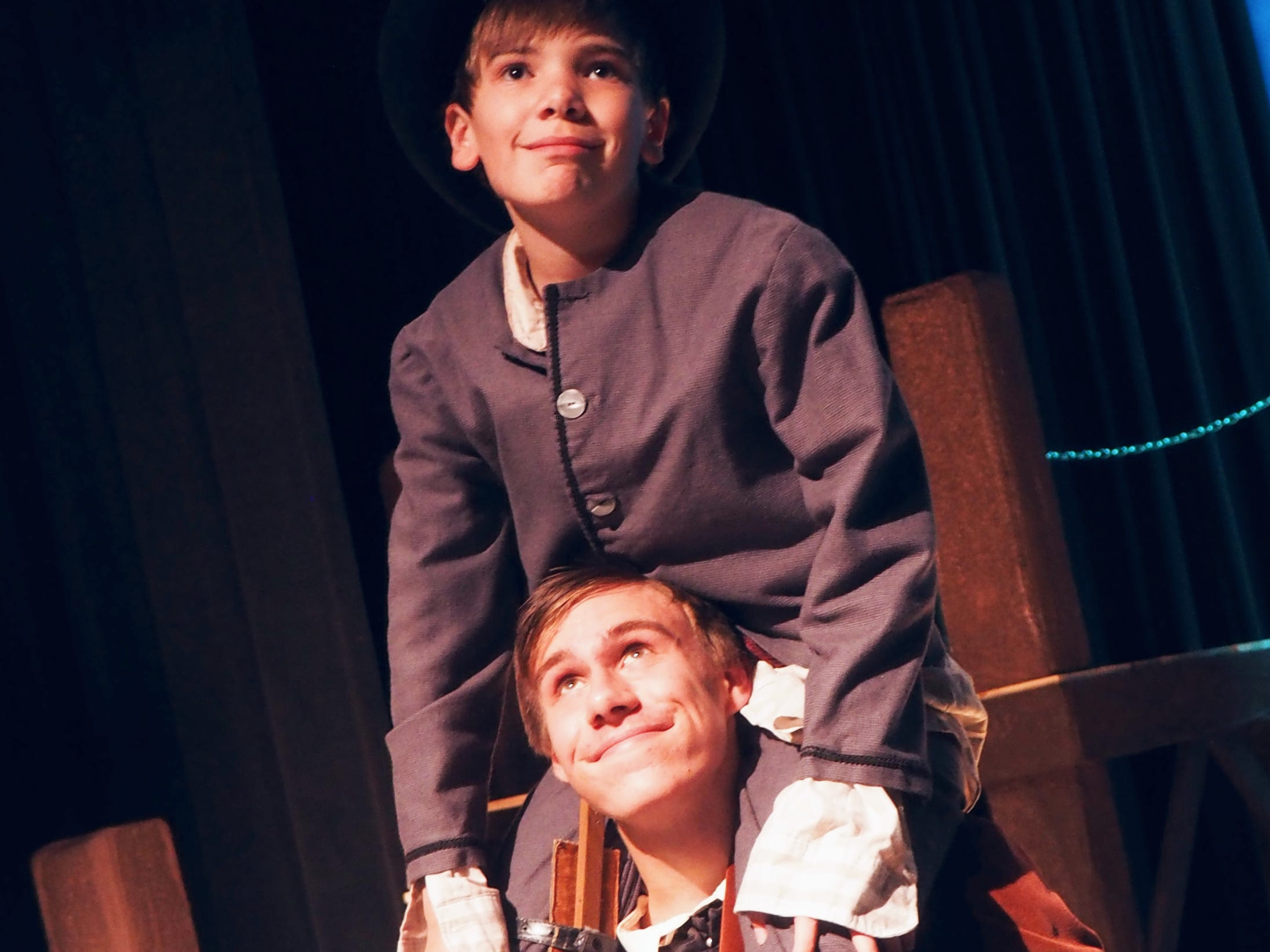 "Bob Cratchit, played by David Bonlander, lifts Tiny Tim, played by Gavin Twohig, onto his shoulders during rehearsals Monday for ""A Christmas Carol,"" which opens on Nov. 1 at the Fond du Lac High School Performing Arts Center."