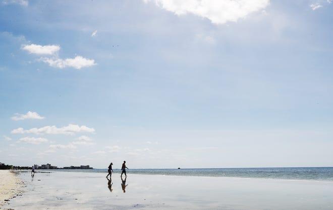 Beachgoers stroll Fort Myers Beach at the Newton Park beach access on Tuesday, Oct. 23, 2018.