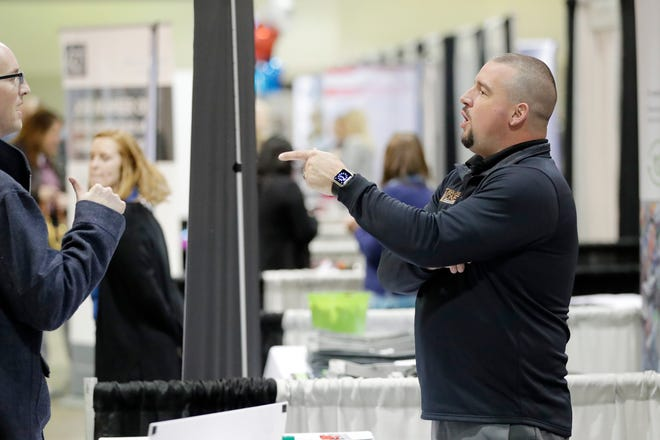 Dean Stoehr, Project Manager at Square One Restoration, works at his company's booth at the Northeast Wisconsin Career Expo at Shopko Hall on Tuesday, October 23, 2018 in Ashwaubenon, Wis.