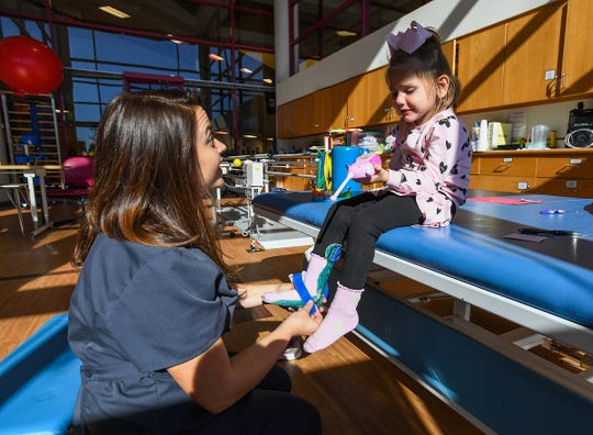 Physical therapist Chelsie Reed works with three-year-old Preslee Holcomb, who has a rare condition called AFM, Monday, October 22, 2018 at the Shriners Hospital for Children in Greenville.