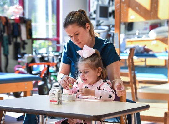 Occupational therapist Krystal Vermillion works with three-year-old Preslee Holcomb, who has a rare condition called AFM, Monday, October 22, 2018 at the Shriners Hospital for Children in Greenville.