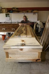 Brad Opheim with one of his blue pine caskets.