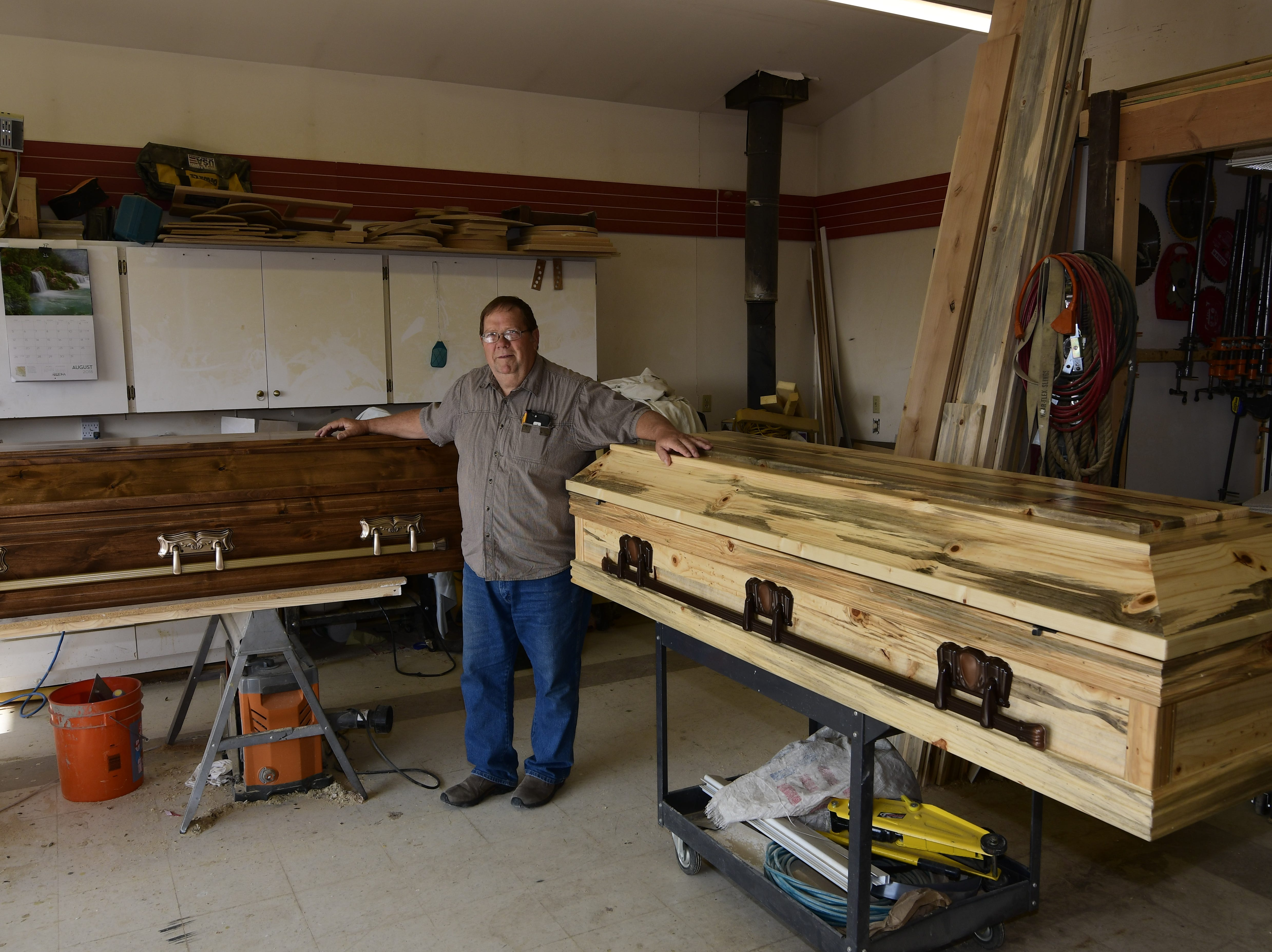 Brad Opheim with two of his creations - a knotty alder casket on the left and a blue pine casket on the right.