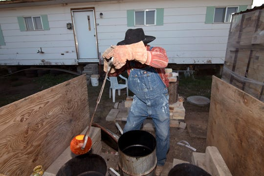 Andy Watson places a red-hot piece of pottery into a metal barrel.