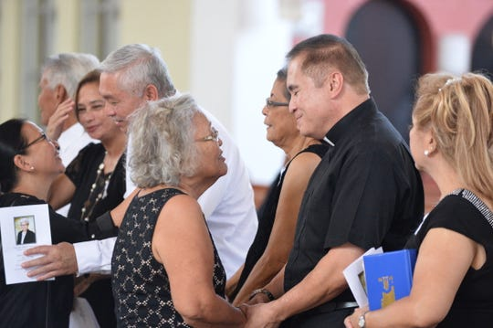 Monsignor James Benavente, his siblings and cousins talk with people paying last respects to his aunt, Sr. Mary Jeanette Leon Guerrero, Oct. 23 at the Dulce Nombre de Maria Cathedral Basilica.