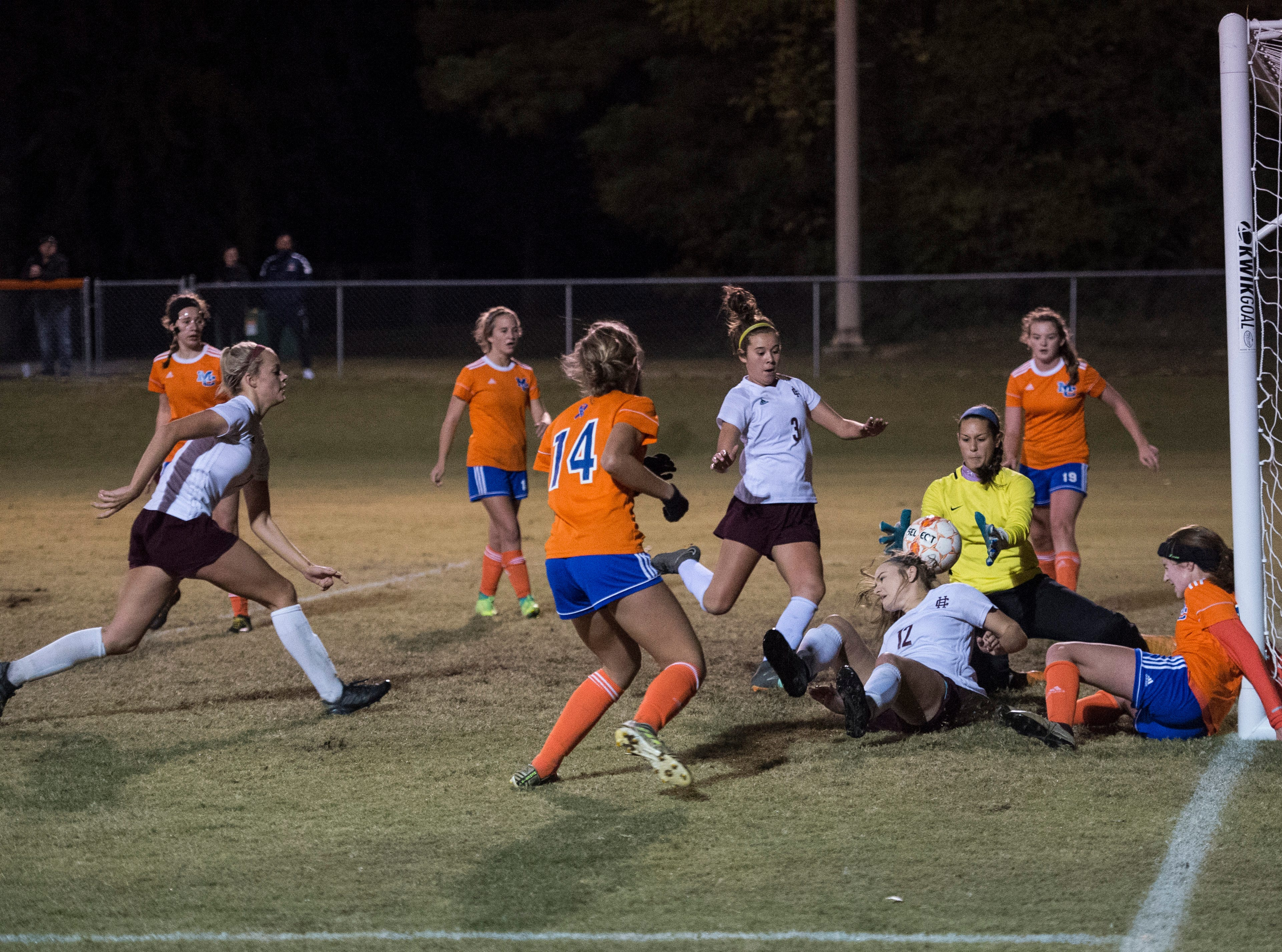 Chaos around the goal as Henderson's Whitnie West (12) attempted to hip the ball towards the goal but was directed into the hands of Marshall County's Carlen Whirley (99)  during the first round of the KHSAA state tournament at Marshall County High School Monday, Oct. 23, 2018.