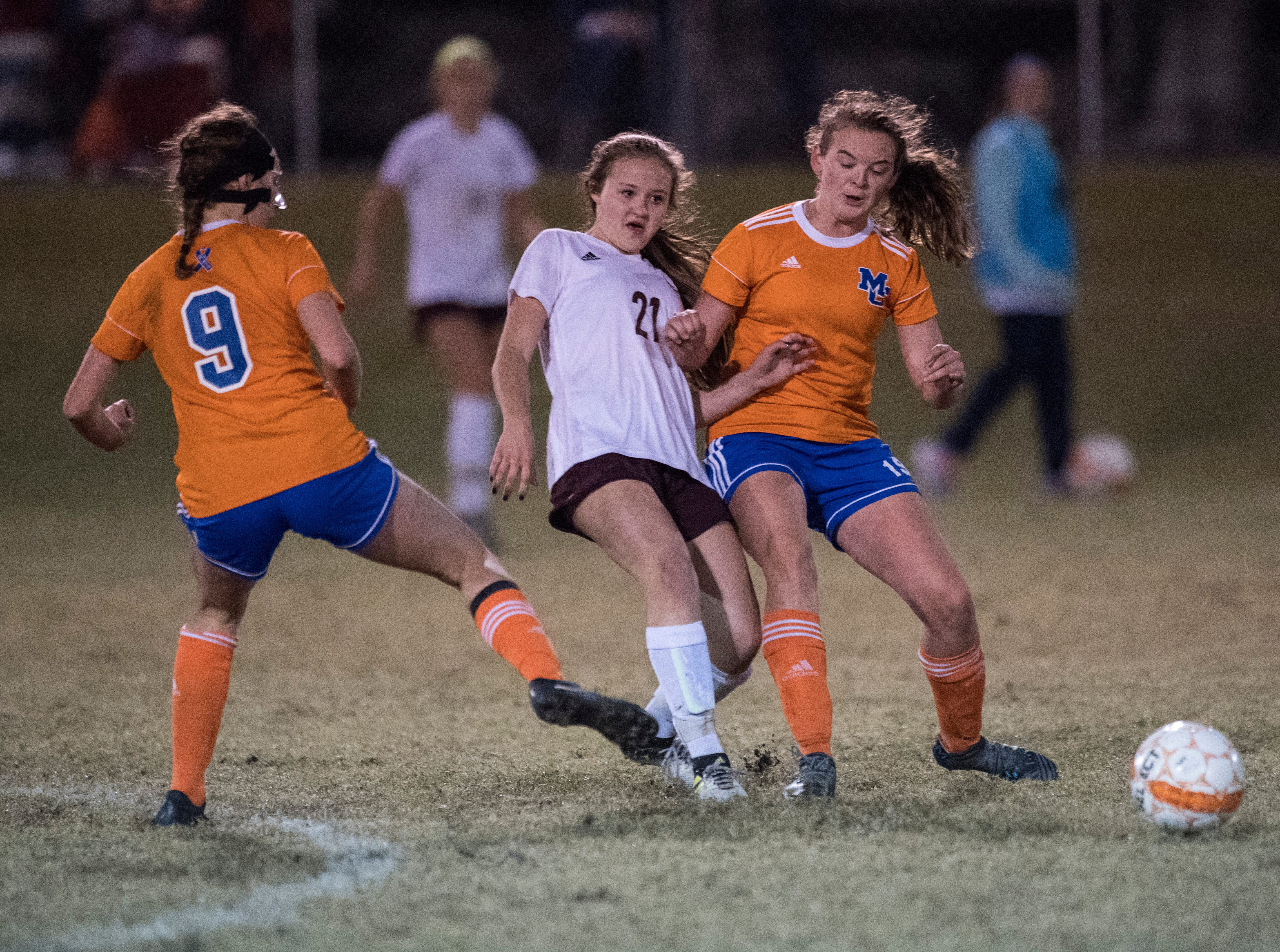 Henderson's Cecilia Palummo (21) passes the ball away from Marshall County defense during the first round of the KHSAA state tournament at Marshall County High School Monday, Oct. 23, 2018.