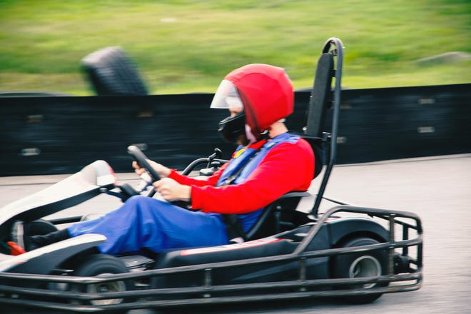A go-kart racer dressed as Mario competes during a Mushroom Rally event