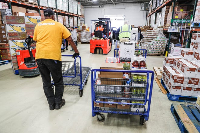 Midwest Food Bank volunteers unload food stuffs after a press conference announcing the expansion of the Food Drop program on Oct. 23, 2018.
