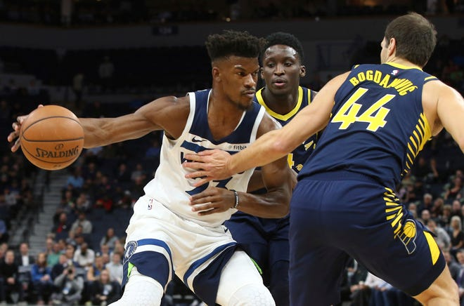 Minnesota Timberwolves' Jimmy Butler, left, tries to work between Indiana Pacers' Victor Oladipo, center, and Bojan Bogdanovic, of Croatia, in the first half of an NBA basketball game Monday, Oct. 22, 2018, in Minneapolis.