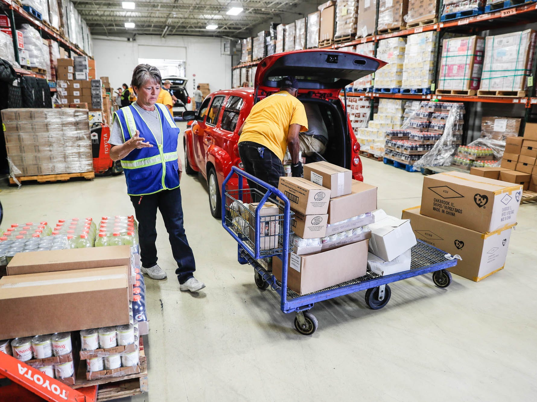 Midwest Food Bank volunteers unload food stuffs after a press conference announcing the expansion of the Food Drop program, which partnered with Indiana's largest hunger relief agencies to make it easier for truck drivers to donate store-rejected food on Tuesday, Oct. 23, 2018.