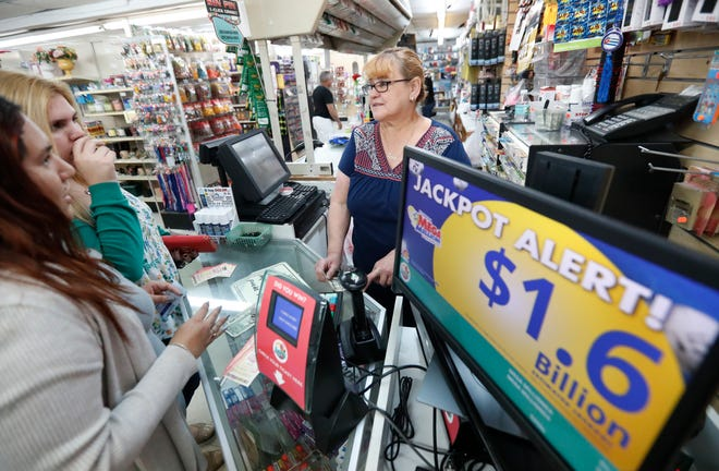 Daysi Lorenzo, center, sells lottery tickets, Monday, Oct. 22, 2018, at La Preferida Superdiscount store in Hialeah, Fla. Lottery players will have a chance at winning an estimated $1.6 billion jackpot in Tuesday night's Mega Millions drawing and an estimated $620 million in Wednesday night's Powerball jackpot.