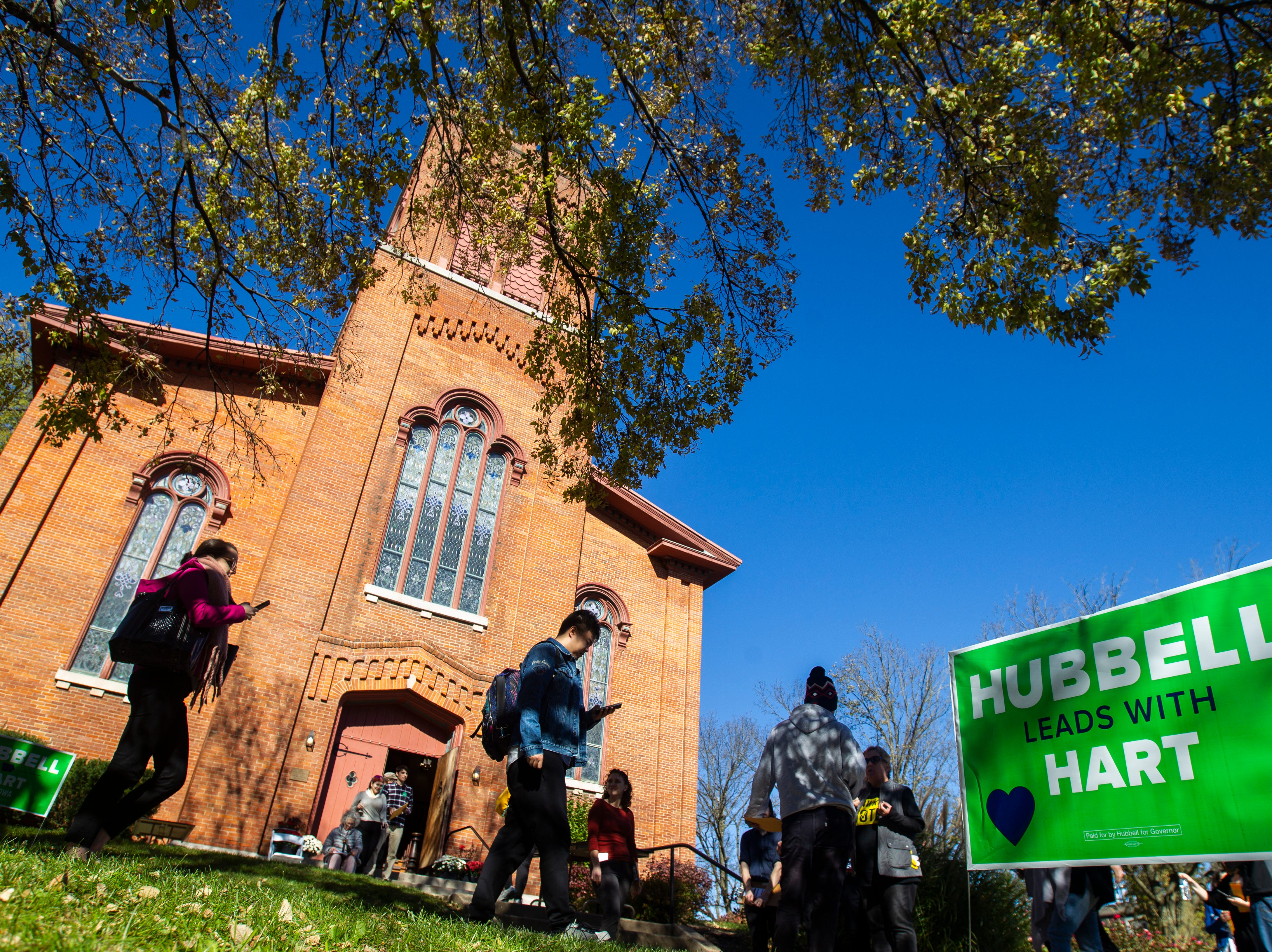 """Fred Hubbell yard signs reading """"Hubbell leads with Hart,"""" line the sidewalk while people make their way towards a """"All Hands on Deck"""" event on Tuesday, Oct. 23, 2018, at Old Brick in Iowa City."""