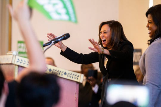 """Sen. Kamala Harris, D-CA, waves to supporters while being welcomed on stage by Deidre DeJear during a """"All Hands on Deck"""" event on Tuesday, Oct. 23, 2018, at Old Brick in Iowa City."""