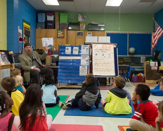 A kindergarten teacher reads to students, including Kaiden Mann, at Rouse Elementary on Oct. 16, 2018.