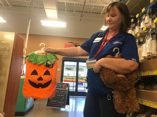 This year's most popular pet costume is a pumpkin, shown by Lisa Wegman at PetSmart.