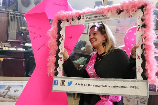 After writing the name of a loved one on the large pink ribbon, Miranda Moretz stands for her picture with a selfie-board the USPS provided on Oct. 23 at the Knoxville Post Office.
