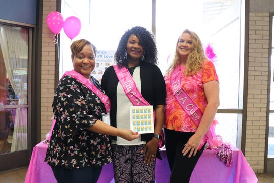 The Knoxville Post Office's breast cancer awareness event organizers stand with a book of the breast cancer research stamps, on Oct. 23.