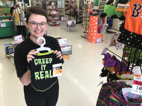 Emily Rogers of Pet Supplies Plus holds one of the pet costumes available for Halloween.