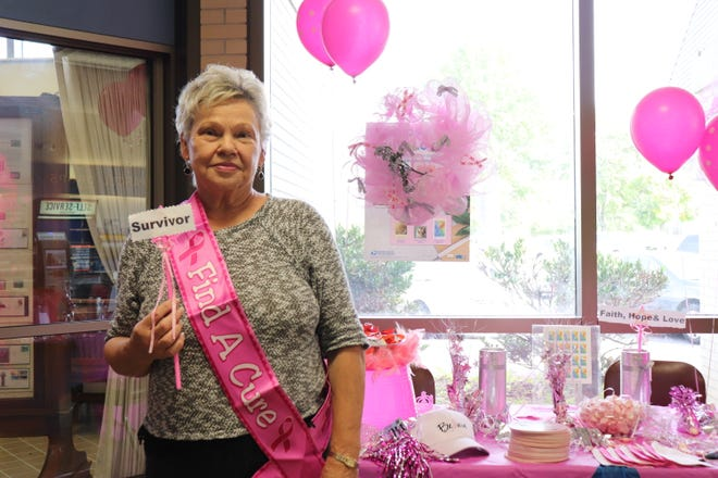 Glenda Stevens, a breast cancer survivor, stands next to the booth in the Knoxville Post Office on Oct. 23 after writing a name on a large ribbon commemorating people affected by the disease.