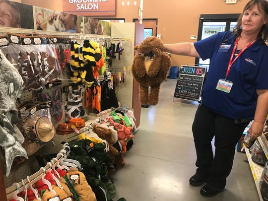 Lisa Wegman of PetSmart shows off a teddy bear costume, next to the rack of other Halloween outfits for pets.