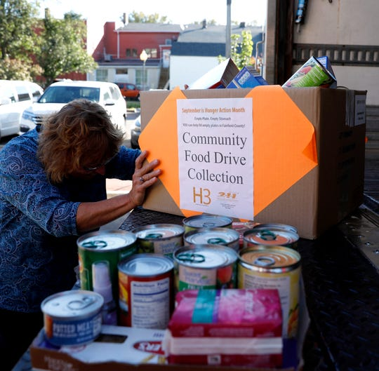 Laura Holton pushes a box of food items into the back of a truck Tuesday morning, Oct. 23, 2018, in Lancaster. Holton and other Fairfield County Job and Family Services employees loaded more than 2,000 lbs. of food they'd collected for the Lancaster-Fairfield Community Action Agency's food bank.